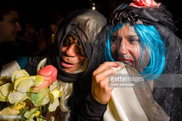 Two men dressed up in mourning clothes and carrying a dildo partying in the streets during the funeral procession Burial of the Sardine the official...