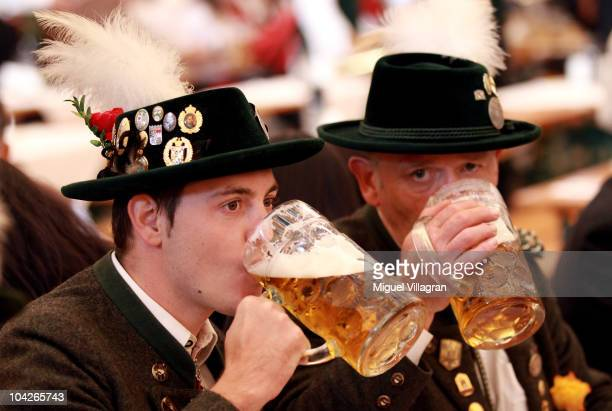 Two men drink beer inside a beer tent during day 2 of the Oktoberfest at Theresienwiese on September 19 2010 in Munich Germany 2010 marks the 200th...