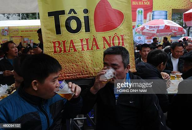 Two men drink free 'bia hoi' next to a poster reading 'I love beer Hanoi' during a local annual beer festival in Hanoi on December 7 2014 Thousands...
