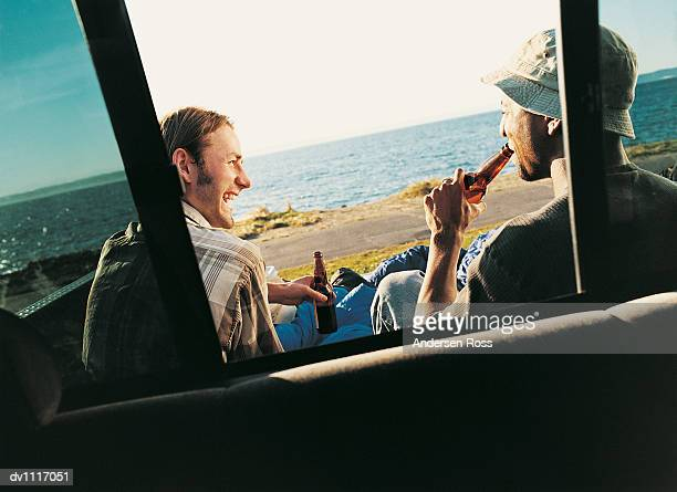 Two Men Drinking Beer by the Sea Seen Through a Window