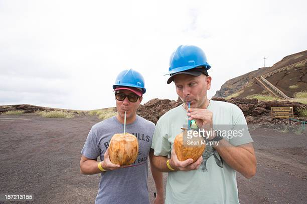 Two men drinking out of coconuts with straws