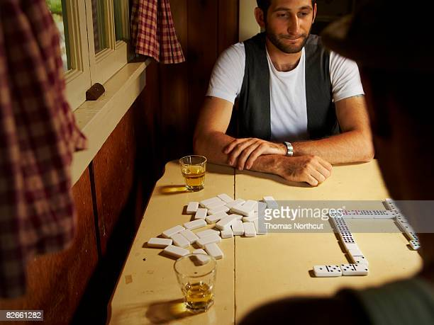 Two men drinking whiskey and playing dominos