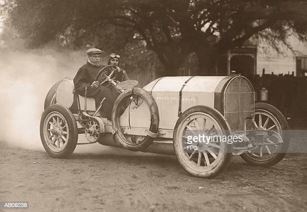 two men driving race car (b&w sepia tone) - 1920 car stock photos and pictures