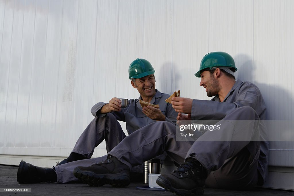 Two men eating lunch beside cargo container, wearing hard hats : Stock Photo