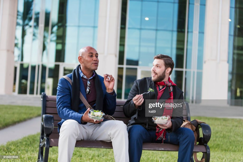 Two men eating lunch on bench outside office building : Stock Photo