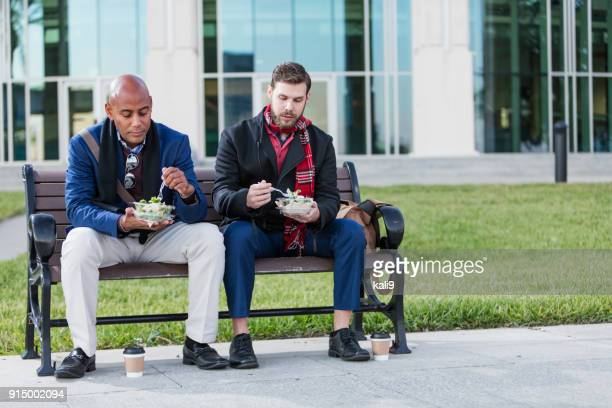 two men eating lunch on bench outside office building - stranger stock pictures, royalty-free photos & images