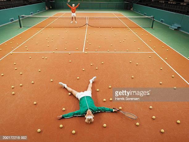 Two men either side of tennis court, one lying on ground amongst balls