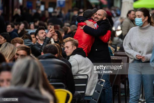 Two men embrace amongst people drinking outside in Soho as non essential retail reopens on April 12, 2021 in London, United Kingdom. England has...