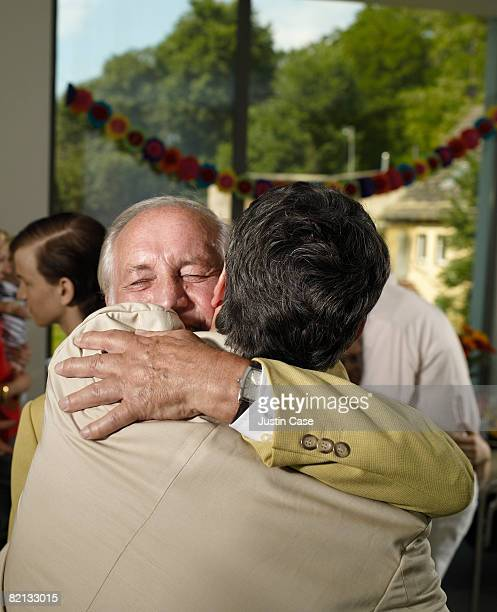 Two men embracing at party