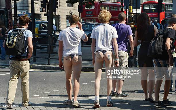 Two men employed to use their buttocks for advertising walk beside Trafalgar Square in central London on July 26 2012 where sunny weather has...