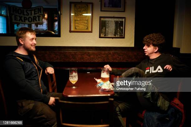 Two men enjoy a drink in The Peveril Of The Peak pub ahead of new Tier-3 Covid-19 restrictions on October 22, 2020 in Manchester, England. Greater...