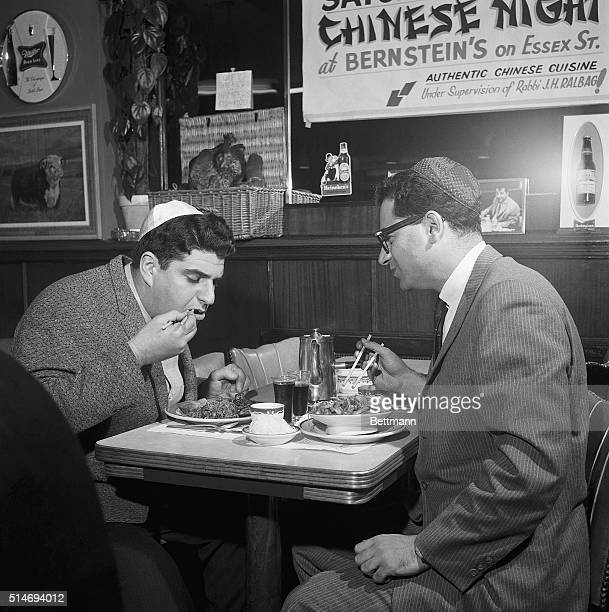 Two men enjoy Chinese cuisine prepared by Chinese chefs within the guidelines of kosher food preparation at a restaurant.