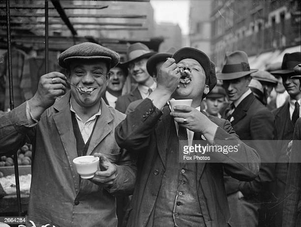 Two men enjoy jellied eels in a Whitechapel street on a Sunday morning