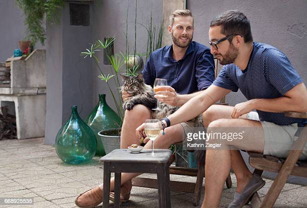 two men enjoying drinks on their terrace