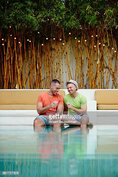 Two men enjoying drinks together by a pool.