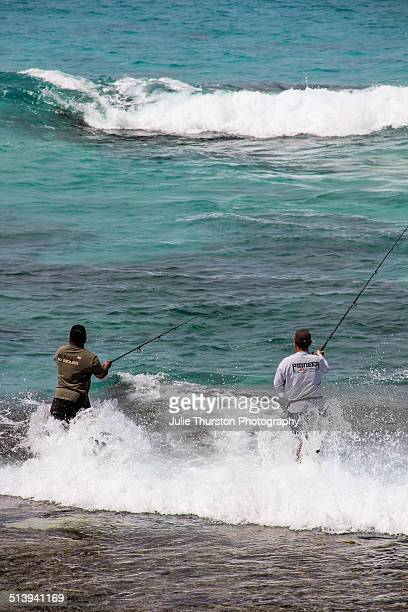 Two Men Enjoying some Recreational Fishing on a Rocky Surface in the Teal Waters of the Pacific Ocean on a Beach in the Vacation Travel Destination...