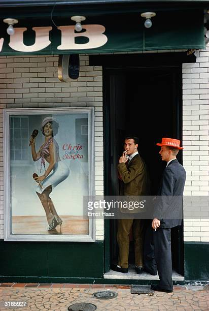 Two men enter a club which advertises ' Chris Queen of the chacha' during Mardi Gras in New Orleans February 1961 One is sporting a bright red boater