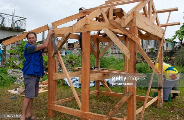 """Two men erect a wood hut in Tacloban,Germany, 15 December 2013. A good two months after typhoon """"Haiyan"""" tore through the Philippines, the survivors..."""