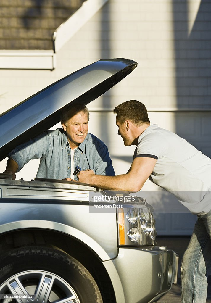 Two men examining engine of car : Foto stock