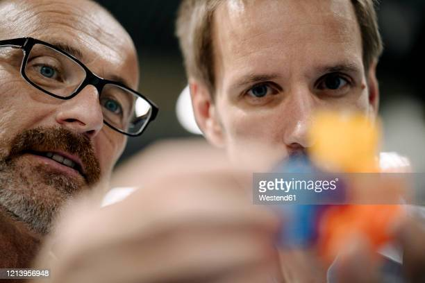 two men examining workpiece in a factory - design professional stock pictures, royalty-free photos & images