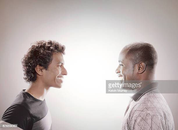 Two men facing each other and smiling