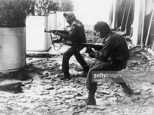 Two men fight on amidst the ruins of the presidential palace in Beirut during the Civil War in Lebanon 26th March 1976