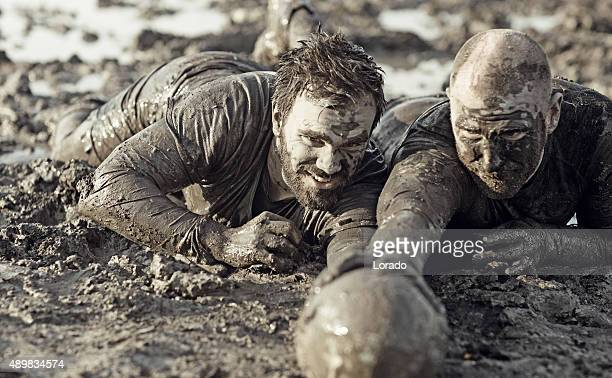 Two men fighting for rugby ball in mud