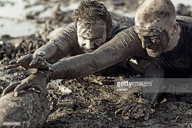 two men fighting for rugby ball in mud - tackling stock pictures, royalty-free photos & images