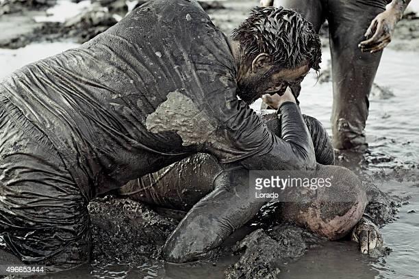 two men fighting in mud