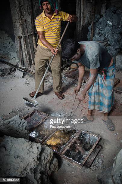 Two men fill the bar mold's with melt lead, without any safety protection. Bangladesh has one of the highest air lead levels in the world. The health...