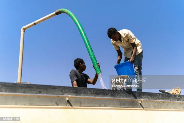 Two men fill water for transport into a tanker on April 03 2017 in Kebri Dahar Ethiopia