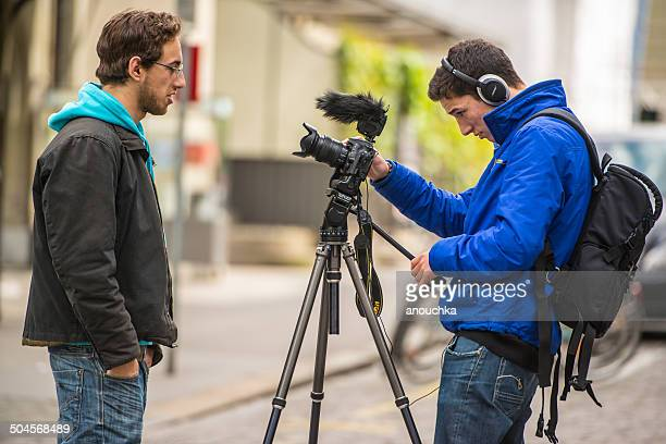 two men filming an interview on bern street, switzerland - nikon stock pictures, royalty-free photos & images