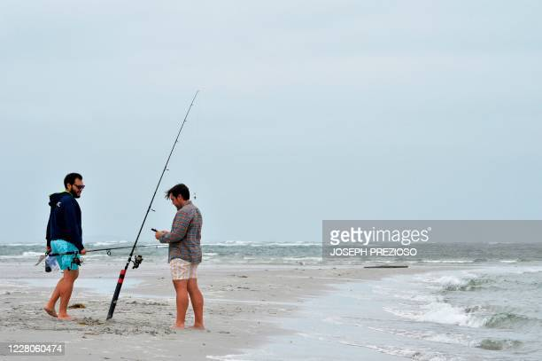 Two men fish from the shore at Wingaersheek Beach in Gloucester Massachusetts on August 15 2020 Over the past summer weekends hundreds of boats have...