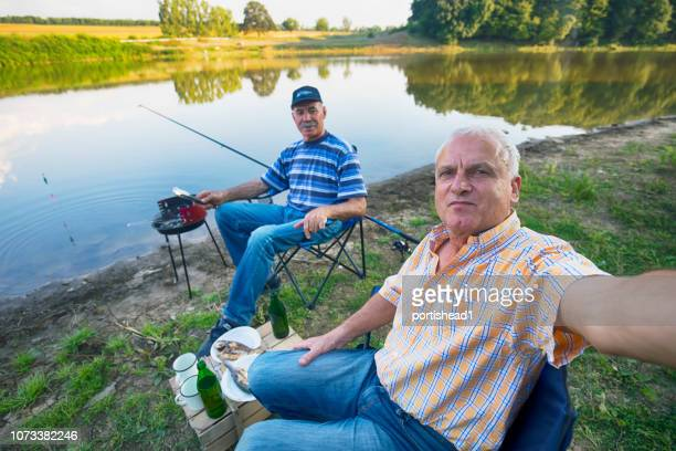 two men fishing and making selfie - amateur stock pictures, royalty-free photos & images