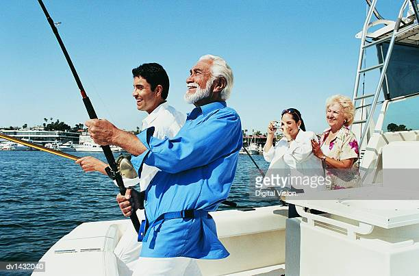 Two Men Fishing at the Stern of a Boat as a Woman Photographs Them