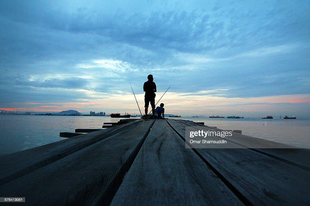 Two men fishing during sunrise : Stock Photo