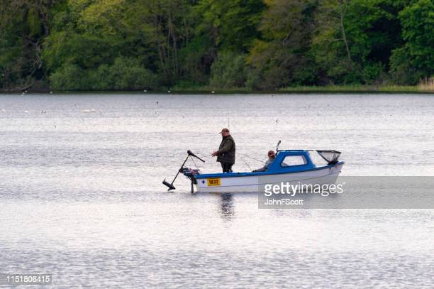 two men fishing from a small boat on a scottish loch - johnfscott stock pictures, royalty-free photos & images