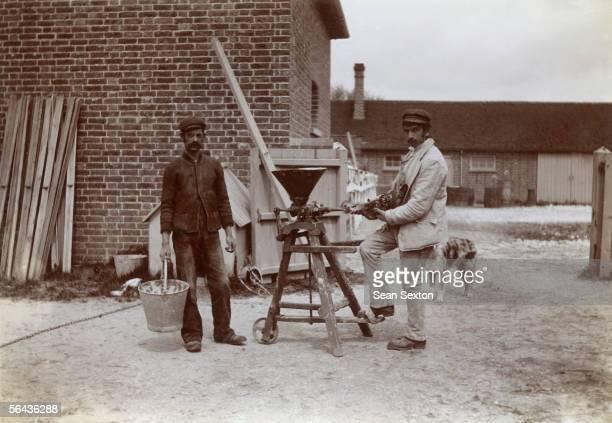 Two men forcefeeding a chicken circa 1895