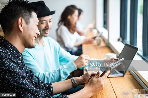 Two men gathering for meeting at cafe with digital devices