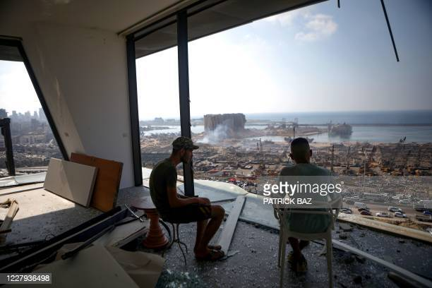Two men gaze at the devastated Beirut port from a damaged building in the nearby neighbourhood of Mar Mikaehl on August 6 two days after a massive...