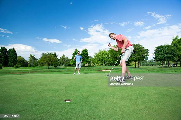 two men golfing on a sunny summer day. - putting - fotografias e filmes do acervo