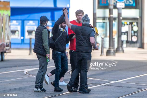 Two men greet one another with a high five in Piccadilly Gardens on March 25 2020 in Manchester United Kingdom British Prime Minister Boris Johnson...