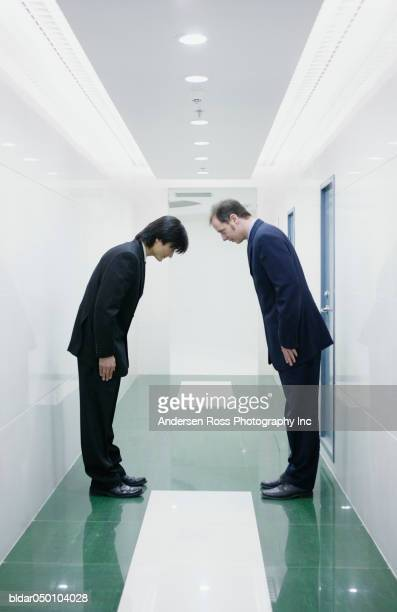 Two men greeting each other in a corridor, Beijing, China
