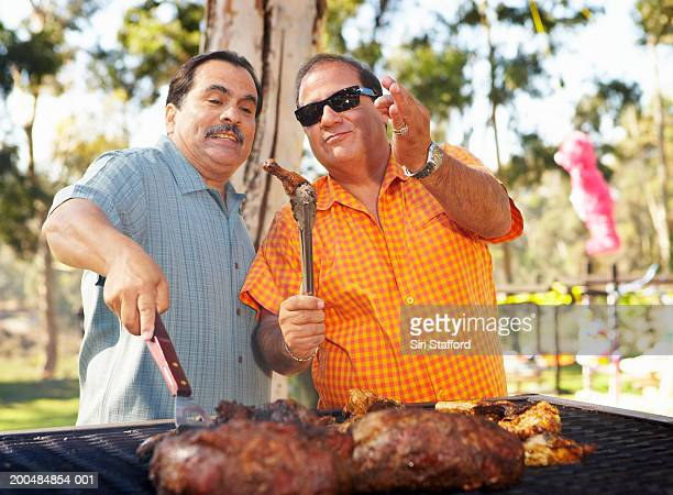 Two men grilling meat in park