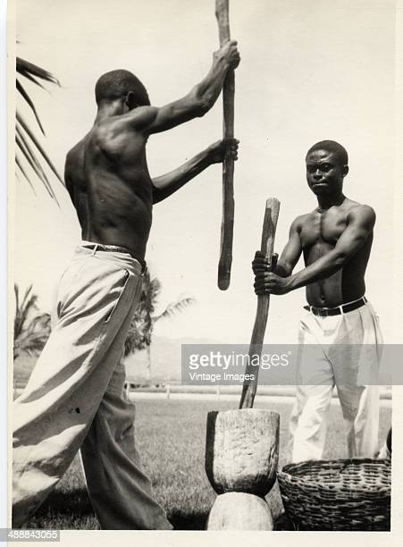 Two men grinding something in a pestle and mortar circa 1940