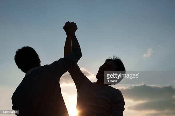 two men hand holding - 若い男性だけ ストックフォトと画像
