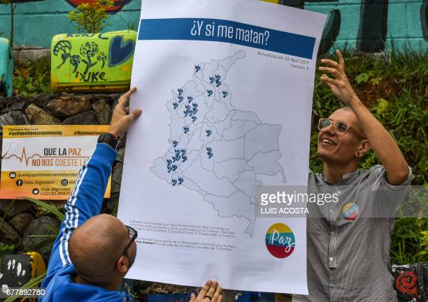 Two men hang a map of Colombia marked with the places where social leaders were murdered after the signing of the historic peace deals with FARC...