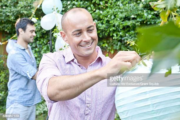 Two men hanging balloons and lanterns preparing for garden party