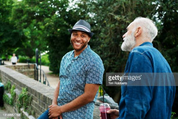 two men hanging out, talking, smiling, leaning on wall - cultures stock pictures, royalty-free photos & images
