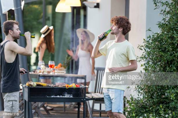 Two men having a beer at barbecue grill